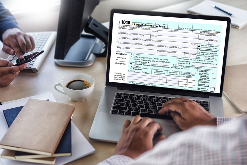 Laptop With Tax Form on Desk