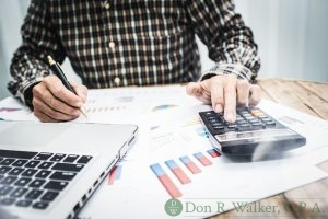 A Man Is Using a Calculator To Work On Tax Information.